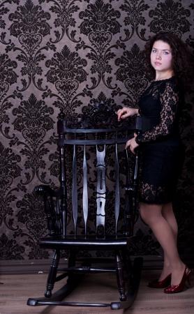 aristocrático: mujer de la aristocracia en el vestido negro de la silla de madera Foto de archivo