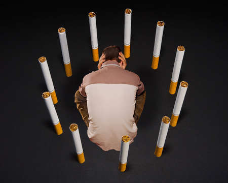 A man sitting  in a cage built of cigarettes