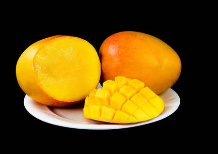 Sliced large mango fruits, on white plate, black background Stock Photo