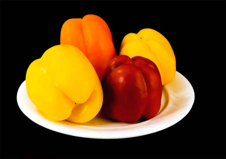 Capsicum in various colors, on white plate, black background