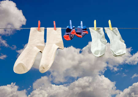 Three pieces of clothing of various size including  on a line drying in the sun