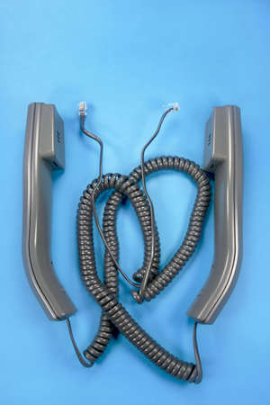 converse: Two unplugged phone handsets on blue background