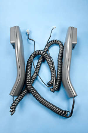 unplugged: Two unplugged phone handsets on blue background