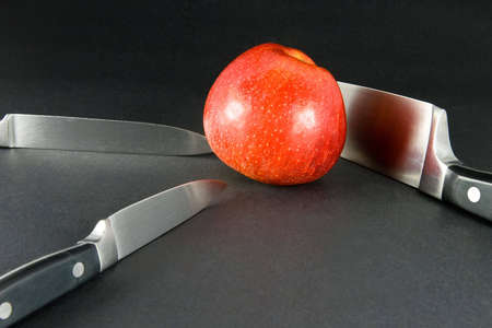 cutting edge: Bright red apple on dark background and three kitchen knives