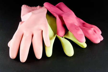 Kitchen gloves of various colors on dark background