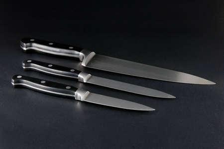 Three steel kitchen knives of various sizes on dark background Stock Photo
