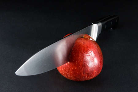 Bright red apple on dark background being cut in half Stock Photo