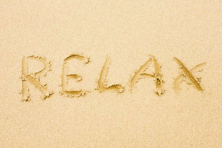 Sandy beach with word Relax written on sand