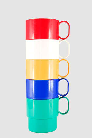 Stack of plastic mugs in various colors Stock Photo