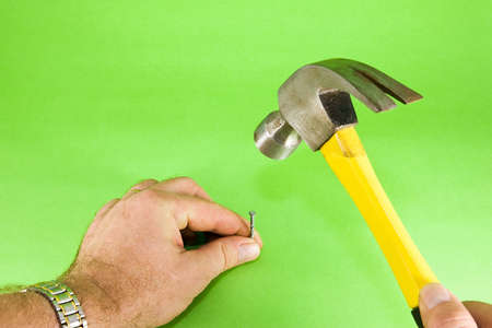 Hammer and nail driven into surface, on green background