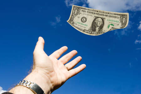 Outstretched hand reaching for a dollar bill floating in the air Stock Photo