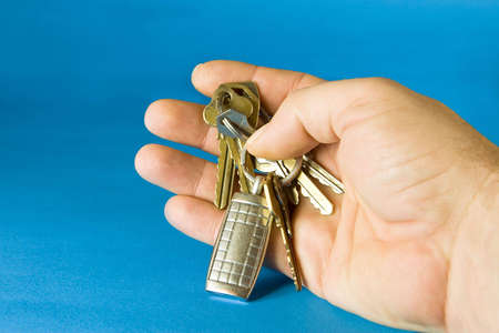keyholder: Bunch of keys with a keyholder on blue background