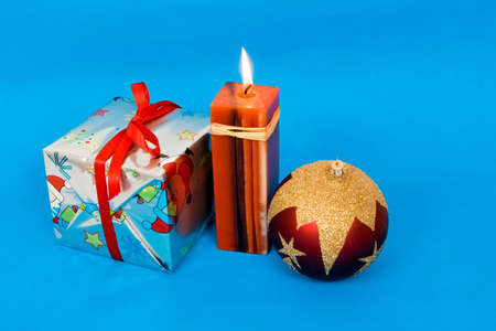 Christmas decorations with a candle on blue background