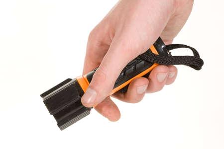 Black and orange flashlight held in hand on white background