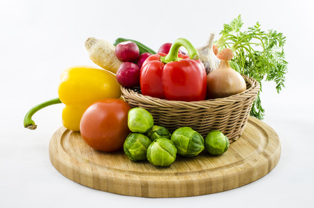 Fresh vegetables in wicker basket on wooden board. photo