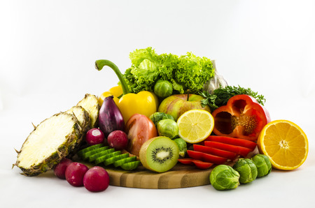 Composition of fresh fruits and vegetables on wooden board. Cut and sliced. photo