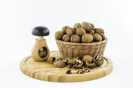 Walnuts in wicker basket on wooden board. photo