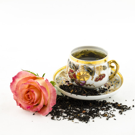 Porcelain tea cup with rose flower and dry tea leaves photo