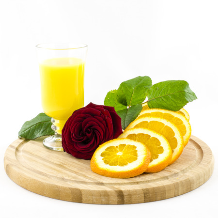 Orange - fruit and juice on wooden board with rose flower photo
