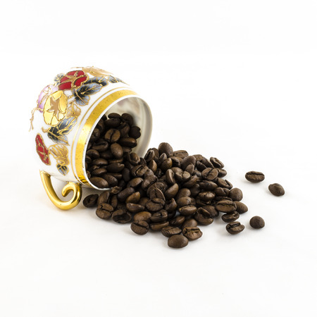 overturned: Overturned porcelain coffee cup with coffee beans isolated on white