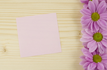 Blank pink card and pink flowers on wooden background photo