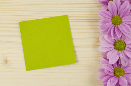 Blank green card and pink flowers on wooden background photo