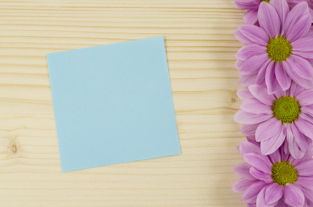 Blank blue card and pink flowers on wooden background photo