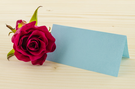 Rose flower with blank invitation card on wooden background photo