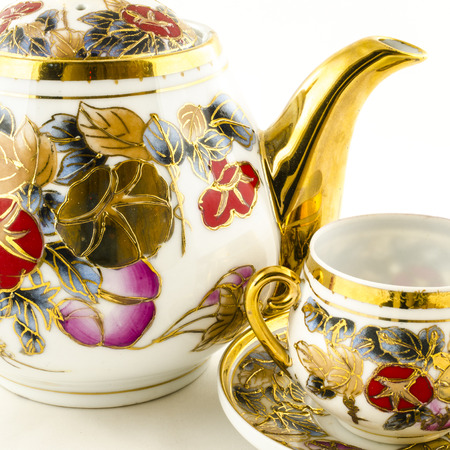Porcelain tea and coffee set with flower motif on white photo