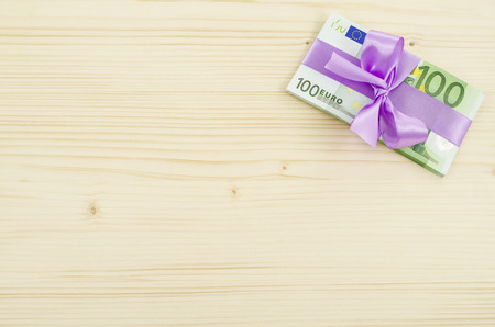 euro bill: Hundred euro bill with pink bow on wooden table Stock Photo
