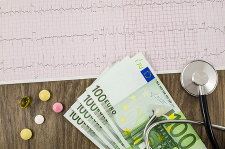 venality: Electrocardiogram with pills, money and stethoscope