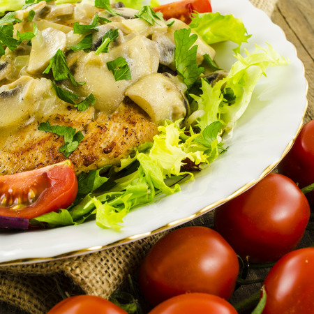 Fried chicken with salad and mushroom sauce photo
