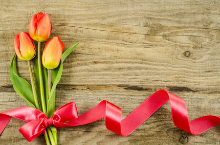 Empty wooden background with colorful flowers and red ribbon photo