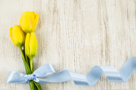 womens day: Empty wooden background with colorful flowers and blue ribbon