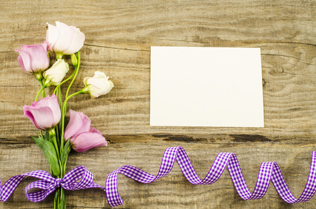 Empty postcard, colorful flowers and ribbon on wooden background