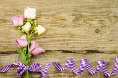 Empty wooden background with colorful flowers and purple ribbon photo