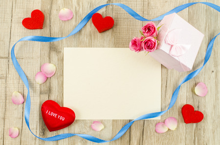 Empty card with rose flower, gift box, heart and ribbon photo