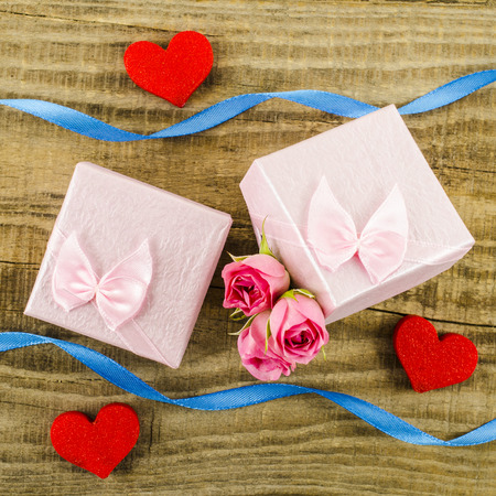 text box: Gift box with rose flower, heart and ribbon on wooden background