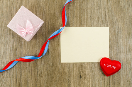 Empty card with heart and gift box on wooden background photo