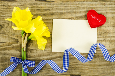 Empty card with flower and ribbon on wooden background photo
