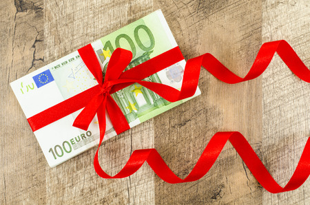 euro bill: Hundred euro bill with red ribbon on wooden table