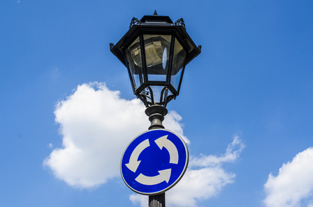 turn about: Roundabout sign on street lantern Stock Photo