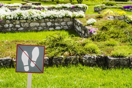 do not: Do not walk on the grass sign