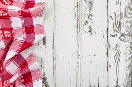 Red folded tablecloth over wooden table photo