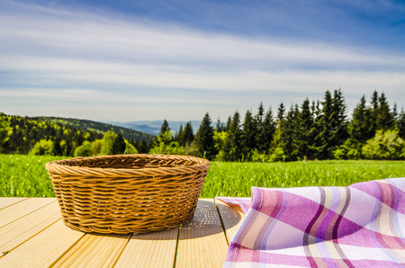 picnic cloth: Violet tablecloth and wicker basket on wooden table Stock Photo
