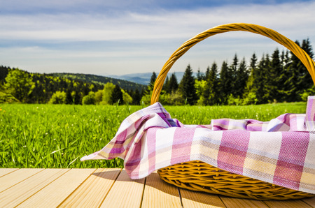 spring landscape: Picnic basket on wooden table Stock Photo