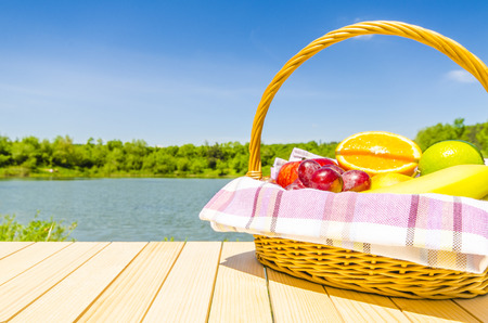 Picnic basket full of fresh fruits on wooden table