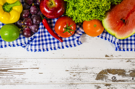 Frame of fresh fruits and vegetables on wooden table photo