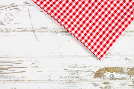 checker: Red tablecloth over wooden table