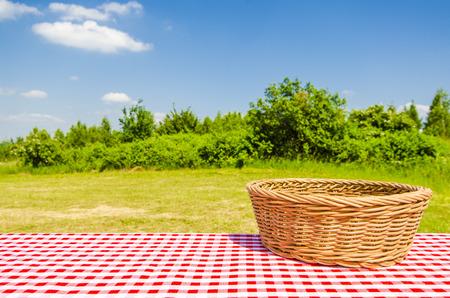 枝編み細工品バスケットと風景の背景、空のテーブル 写真素材